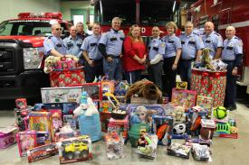 "Members of the Saranac Lake Volunteer Fire Department pose with the gifts and Patti Ploof representing ""Holiday Helpers"""