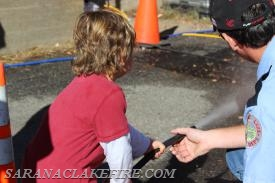 "Lieutenant Doug Peck instructs a child on the proper use of a fire extinguisher using the ""Bullex"" simulator."