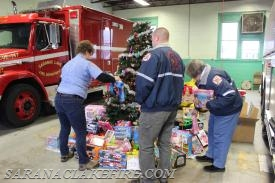 A group of SLVFD members put up Christmas tree and a start with a pile of toys.