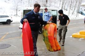 The US Postal Service arrives with gifts collected from the Saranac Lake Postal Workers.