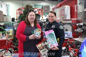 Patti Ploof receives donations from the SLPD from Officer Reyanin Peck.
