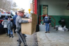 NYSP Troop B Commander, Major John H. Tibbitts Jr. carries in a big box of toys donated by the employees of NYSP Troop B