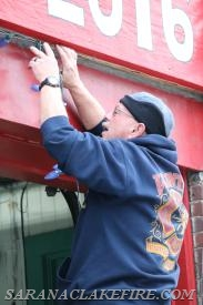 As part of the holiday cheer, SLVFD members decorated the station.  Here SLVFD Dive Captain Ken McLaughlin affixes lights above the first bay doors.