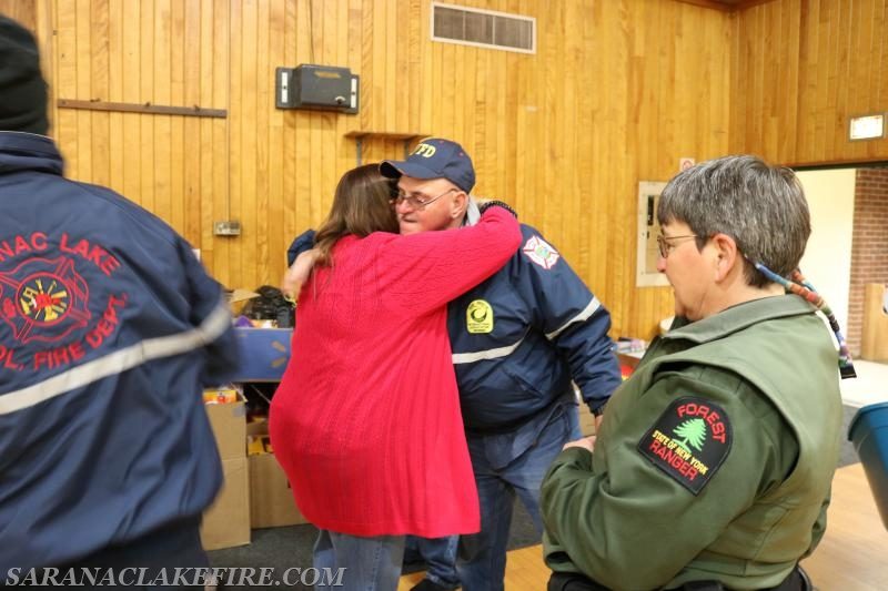 Holiday Helpers Co-Chair Patti Ploof hugs SLVFD Assistant Chief Andy McGill.