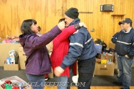Holiday Helpers Co-Chairs Patti Ploof and Dawn Rogers give SLVFD Chief Brendan Keough a hug at the end of the day.
