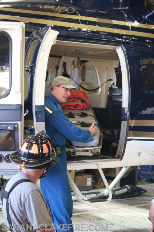 Flight Paramedic Bill Martin provides instruction on loading the patient litter onto the receptacle in the helicopter.