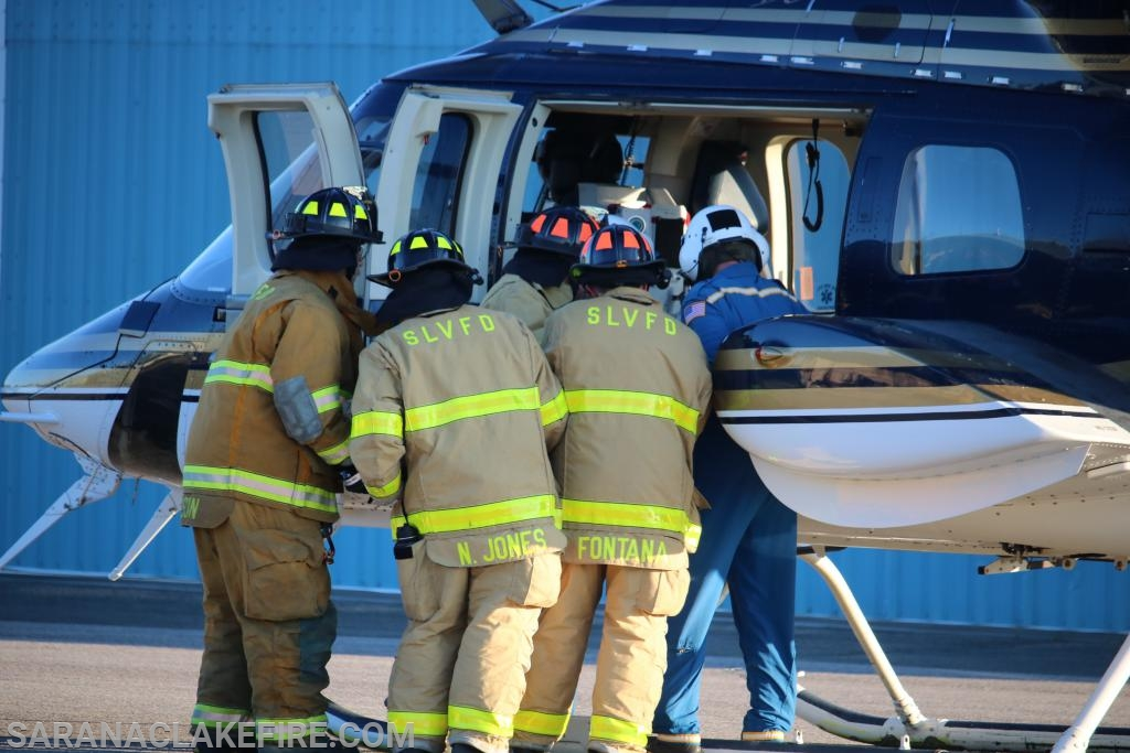 A group of SLVFD firefighters loading and unloading onto a running helicopter.
