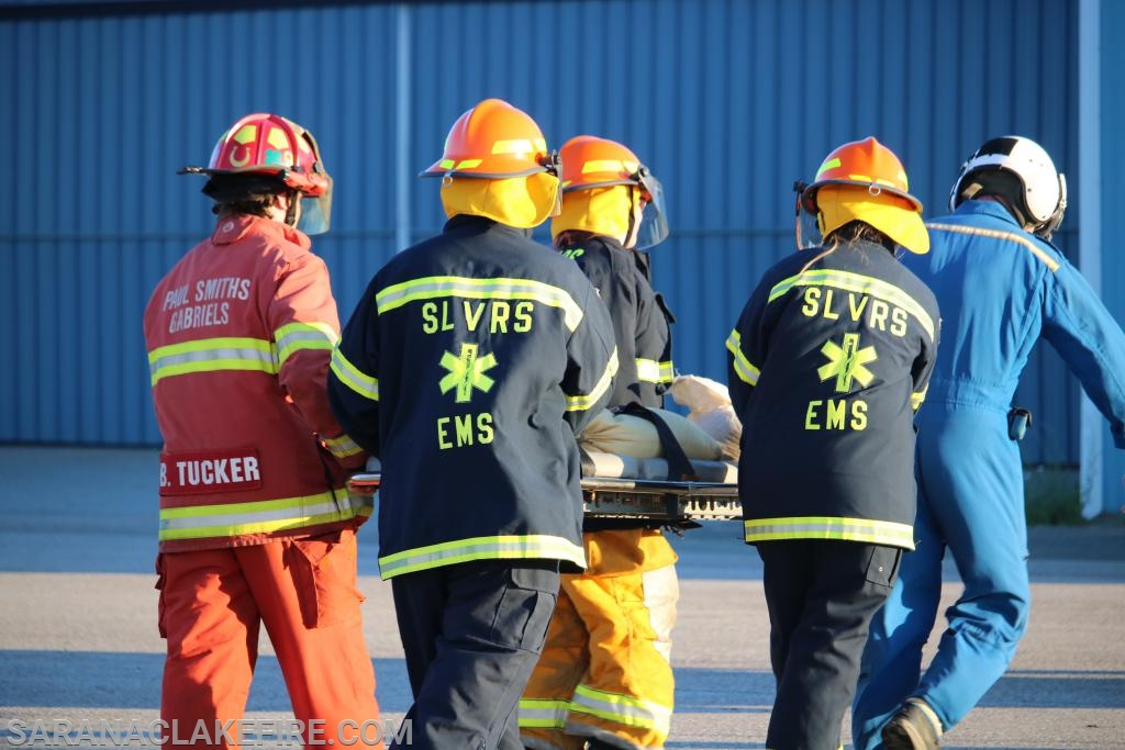 A group of SLVRS members and PSGVFD firefighters loading and unloading onto a running helicopter.