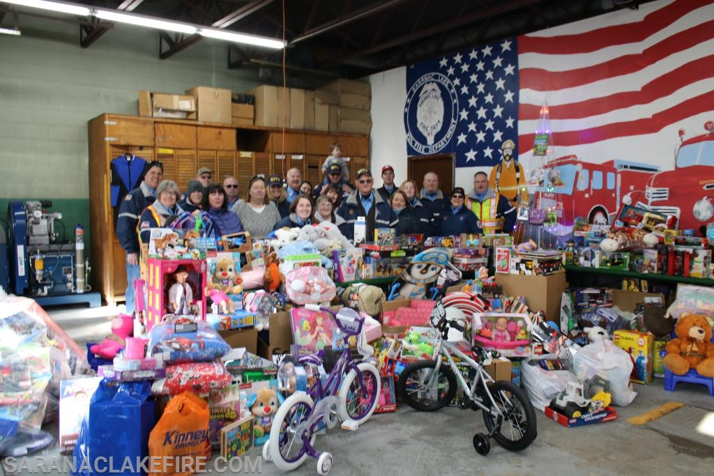 Members of the SLVFD, SLVFD Auxiliary, and the Holiday Helpers organization pose behind a huge pile of toys collected today...