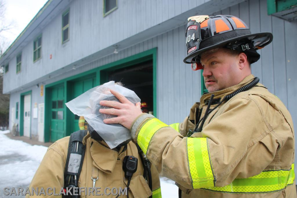 """Lieutenant Michael Knapp applies wax paper to a firefighters face mask...  All of todays training was done """"blacked out"""" the wax paper blinds the firefighter just as smoke in a real fire would do."""