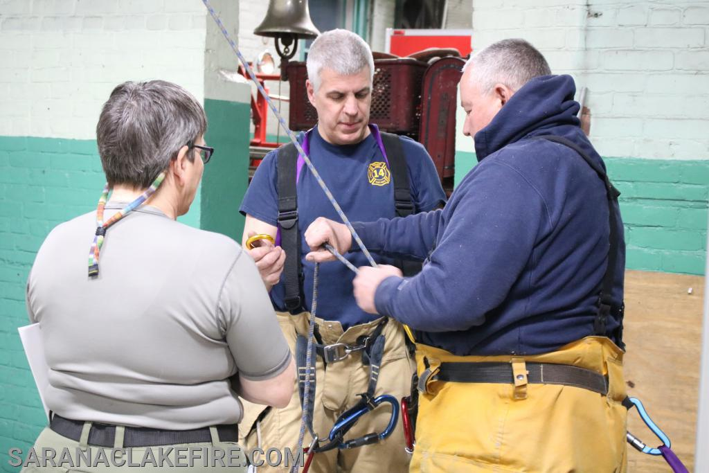 The belay man manages the belay line in the event a firefighter falls.  Notice the additional carabiner clip at the rear of the belay man.  He is fastened to an immovable object in the event he must absorb the weight of a falling firefighter.