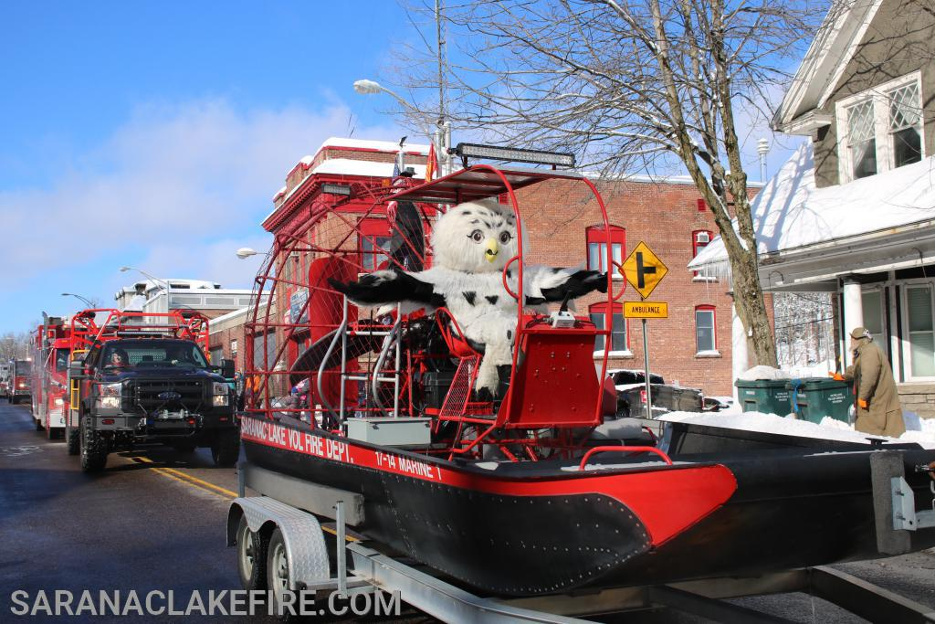 "Saranac Lakes Winter Carnival  Mascot ""Sara the Snowy Owl""  hitches a ride through the Parade  atop SLVFD's Marine 1"