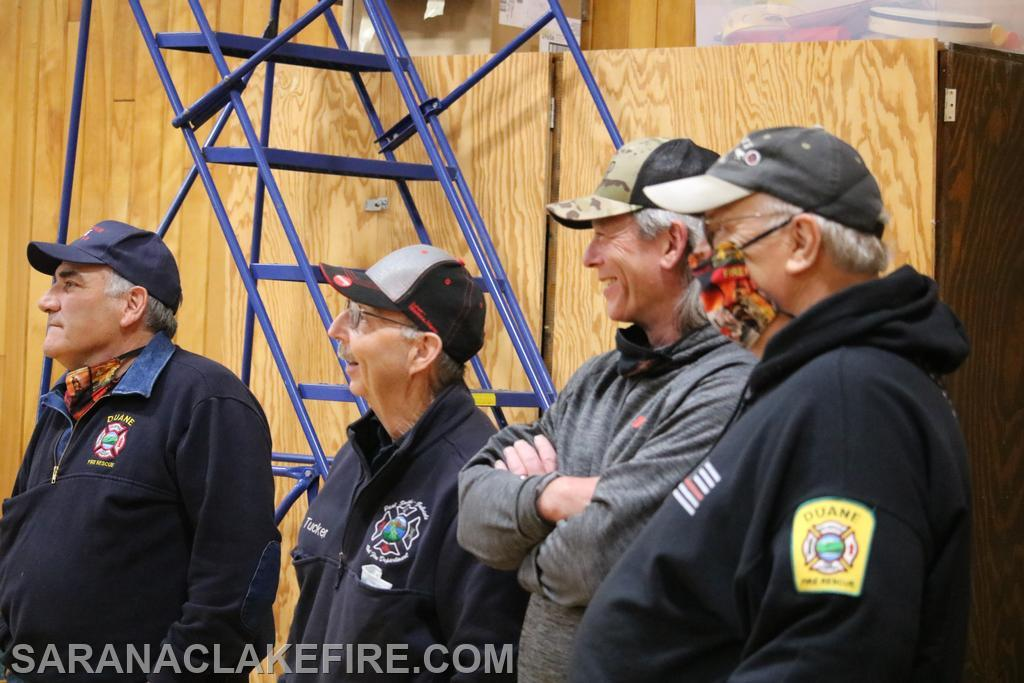 A contingent of firefighters from Duane and Paul Smiths-Gabriels watch on.  L-R Scott Glenny, Steve Tucker, Ned Lemieux, and Bill Brunelle.