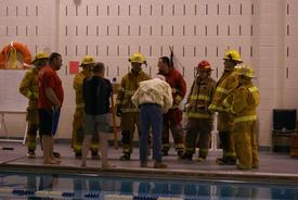 A dry group of firefighters receive instruction from Team Lifeguard Systems President and Founder Butch Hendrick prior to taking the plunge...