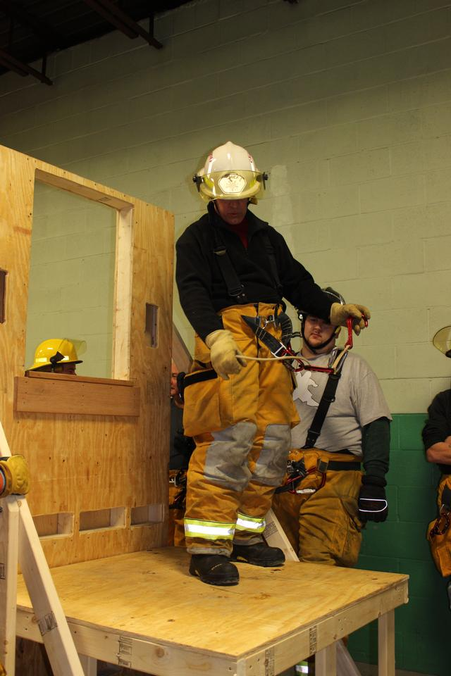 Chief Keough stands on training prop, demonstrating use of SLVFD's bailout components