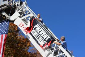 Captain James D'Ambro and Chief Brendan Keough hang a fire prevention banner on the boom of Ladder 144 which rose above broadway on display for this years open house.